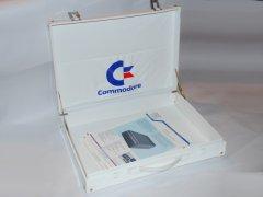 Das Innere der  Aktentasche, auch mit dem Commodore-Logo. Im Inneren der Tasche enthält eine Broschüre des Commodore SFS 481 Laufwerk.